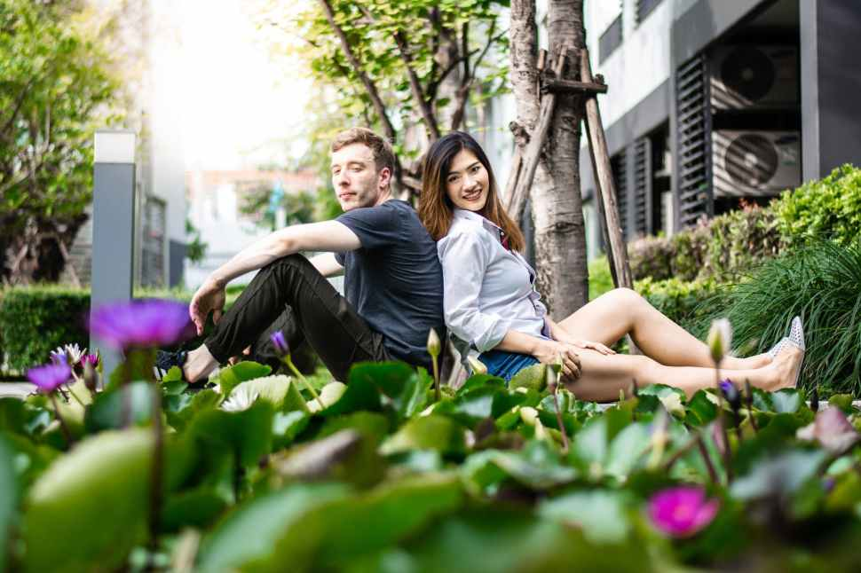 man and woman leaning against each other near tree trunk