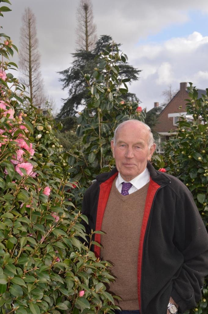Een zichtbaar trotse kweker Kortmann tussen zijn Nationale  Plantcollectie van Camellia